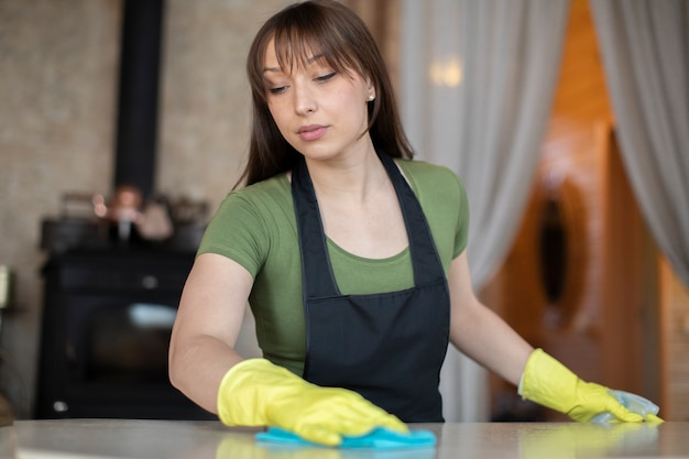 Mädchen in gelben handschuhen und schwarzer schürze mit sprühgerät wischt tischoberfläche mit stoff ab