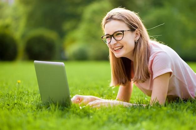 Mädchen in gläsern mit laptop, der auf dem rasen liegt