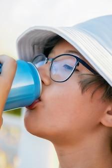 Mädchen in gläsern und panamahut trinkt erfrischungsgetränk in blechdose
