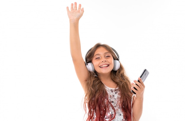 Mädchen in glitzerndem kleid, mit großen weißen kopfhörern und schwarzem handy in der hand ist wirklich glücklich, jemanden isoliert zu sehen