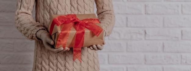 Mädchen in gummihandschuhen hält ein geschenk warmer strickpullover das konzept der ferien