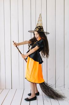 Mädchen in halloween-kostüm, das besenflug im studio nachahmt