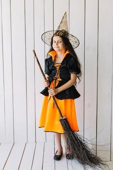 Mädchen in halloween-kostüm mit dem besen, der im studio aufwirft
