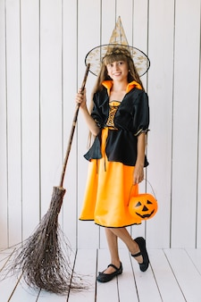 Mädchen in halloween-kostüm mit dem korb und besen, die im studio aufwerfen