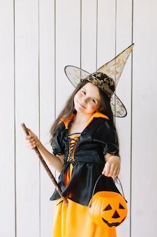 Mädchen in halloween-kostüm mit dem kürbiskorb, der im studio aufwirft