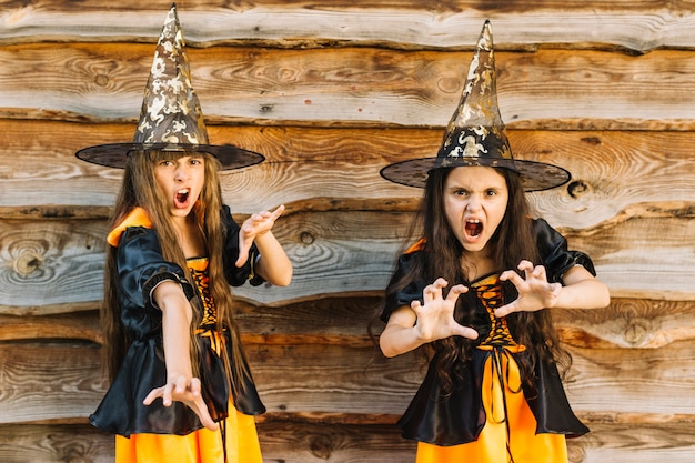 Mädchen in halloween-kostümen, die einen bösen zauberspruch vortäuschen