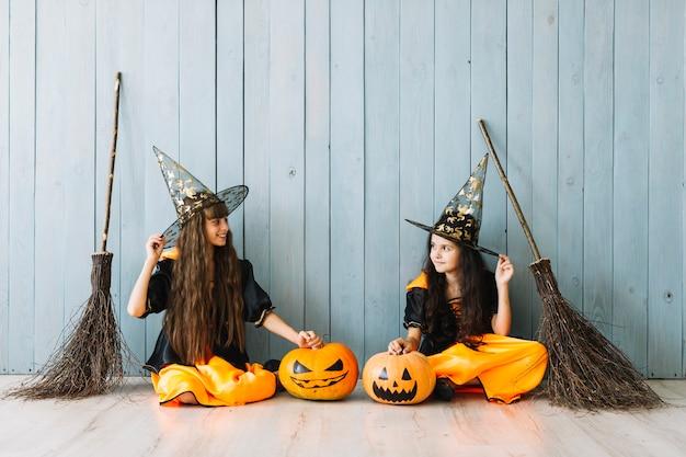 Mädchen in halloween-kostümen mit spitzen hüten und besen sitzen am zaun