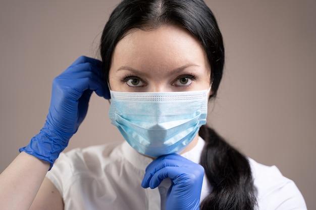 Mädchen in handschuhen, die eine maske aufsetzen