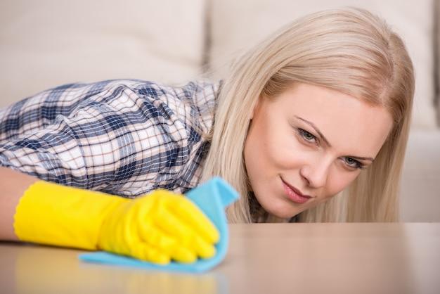Mädchen in handschuhen säubert den tisch mit einem lappen.