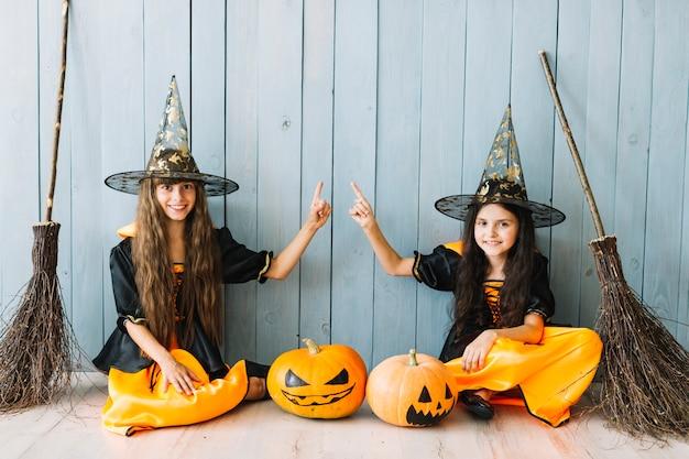 Mädchen in hexenkostümen mit den besen, die durch zaun sitzen