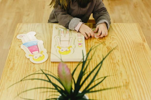 Mädchen in ihrer schule, die mit einem puzzlespiel des menschlichen körpers spielt, um anatomie zu lernen.