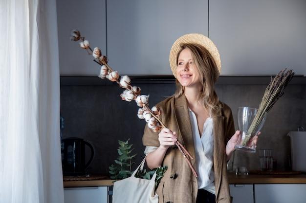 Mädchen in jacke mit einkaufstasche und baumwollpflanze in einer küche