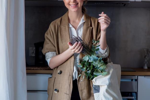 Mädchen in jacke mit einkaufstasche und pflanzen in einer küche