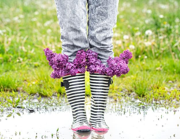 Mädchen in jeans und gestreiften gummistiefeln mit einem strauß frischer lila blumen in einer pfütze unter dem gras.