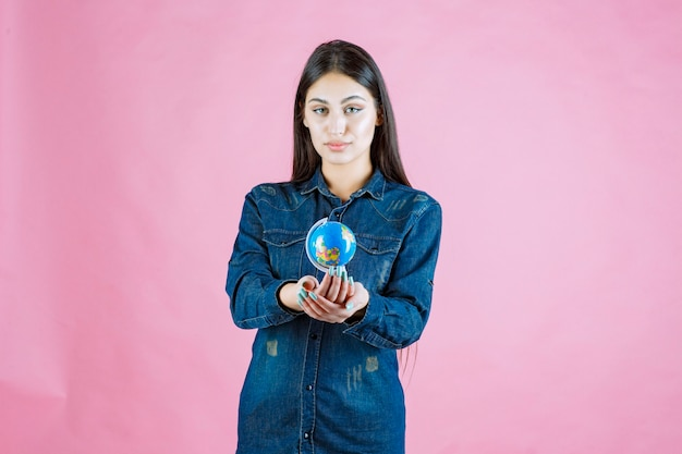 Mädchen in jeansjacke, die ihrem freund ihren minikugel anbietet