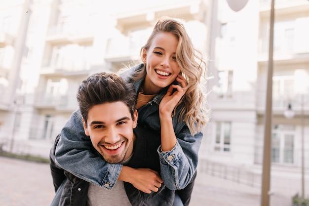 Mädchen in jeansjacke umarmt freund. lächelndes kaukasisches paar, das zusammen auf der straße aufwirft.