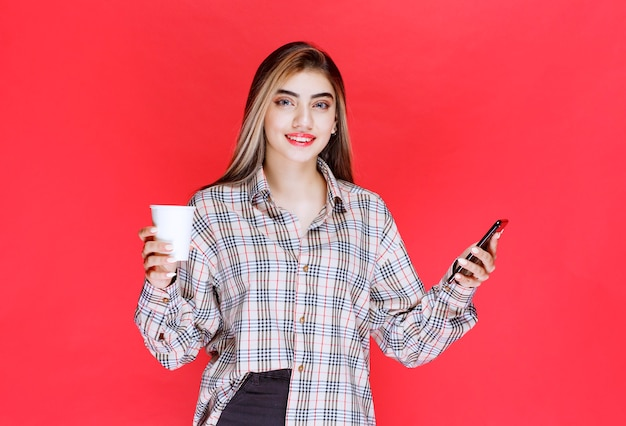 Mädchen in kariertem hemd, das eine tasse getränk hält und mit ihrem smartphone spielt