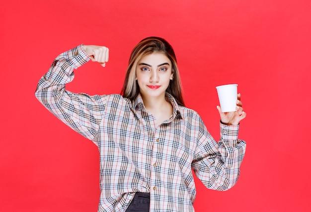Mädchen in kariertem hemd, das eine weiße einweg-kaffeetasse hält und ihre macht zeigt