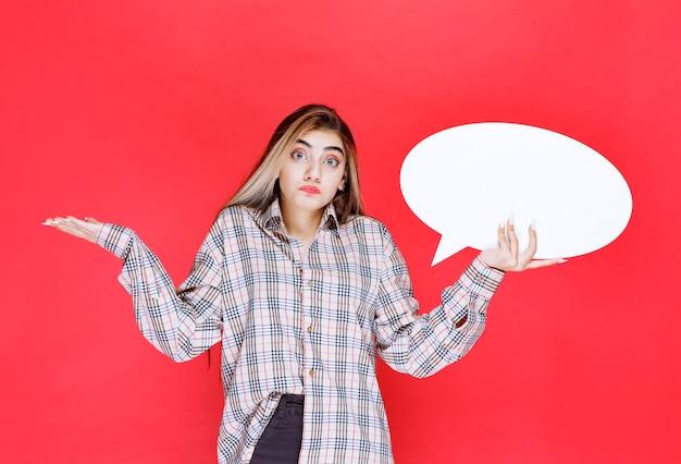 Mädchen in kariertem pullover, das ein ovales ideaboard hält, sieht unerfahren und verloren aus