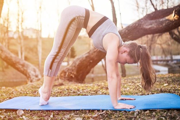 Mädchen in katzenpose auf yogamatte im park