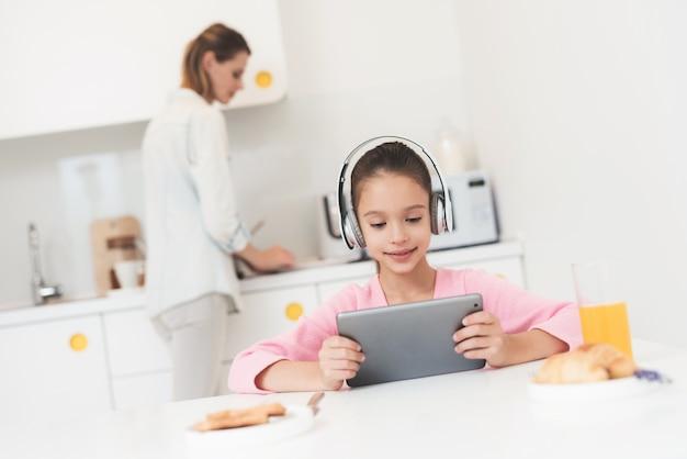 Mädchen in kopfhörer und tablet sitzt in der küche