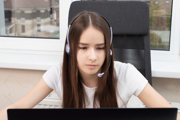 Mädchen in kopfhörern mit einem mikrofon aus einem callcenter zu hause
