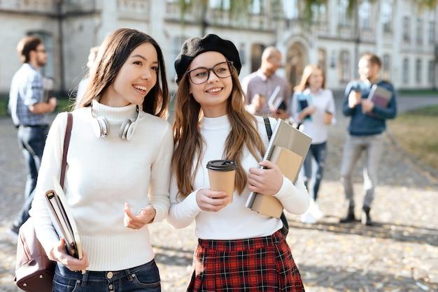 Mädchen in kopfhörern steht neben ihrer freundin und lächelt.