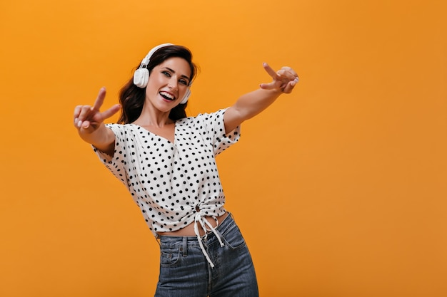Mädchen in kopfhörern zeigt anzeichen von frieden und hört musik mit kopfhörern. lächelnde frau mit dunklem welligem haar im weißen tupfenhemd, das spaß hat.