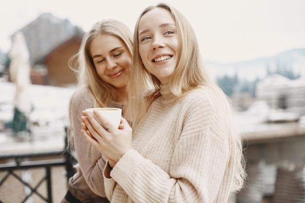 Mädchen in leichten kleidern. winterkaffee auf dem balkon. glückliche frauen zusammen.