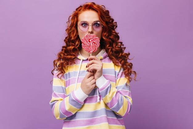 Mädchen in lila brille und süßem sweatshirt leckt riesiges karamell und schaut nach vorne