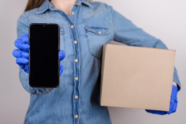 Mädchen in medizinischen handschuhen demonstriert smartphone und hält pappkarton lokalisierten grauen hintergrund