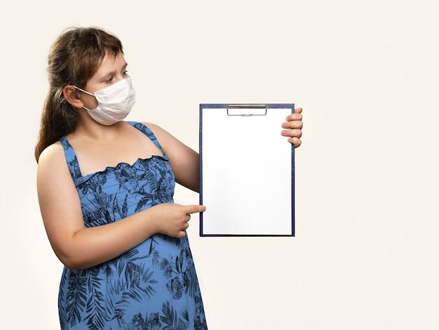 Mädchen in medizinischer gesichtsmaske hält klemmbrett in ihren händen und zeigt etwas darauf