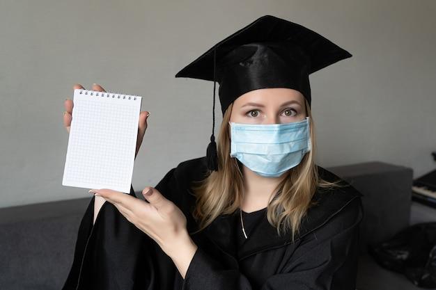 Mädchen in medizinischer maske mit abschlusskleid, das ein kleines notizbuch auf grauem hintergrund hält holding