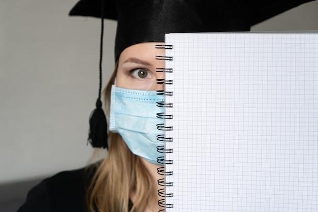 Mädchen in medizinischer maske mit abschlusskleid, das ein notizbuch über ihrem gesicht auf grauem hintergrund hält