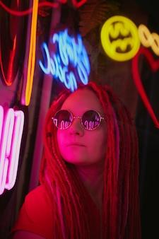Mädchen in neonlichtern, schöne frau mit sonnenbrille, mit rosa haaren, mit dreadlocks-zöpfen,
