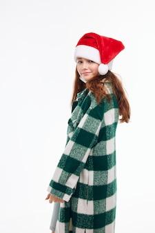 Mädchen in neujahrskleidung weihnachtsmütze lächeln, was hellen hintergrund zu tun. hochwertiges foto
