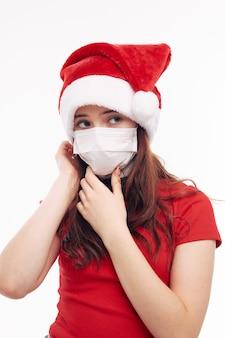 Mädchen in neujahrskleidung weihnachtsmütze medizinische maske urlaub neujahr. hochwertiges foto