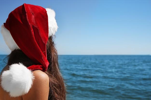 Mädchen in nikolausmütze am strand. weihnachtskonzept