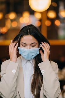 Mädchen in nimmt ihre schützende medizinische gesichtsmaske ab