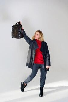 Mädchen in oberbekleidung hält eine tasche in der hand