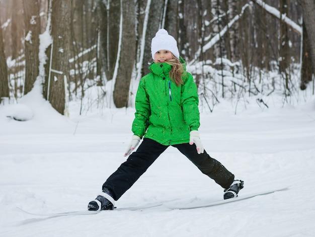 Mädchen in overalls macht dehnübungen auf skiern