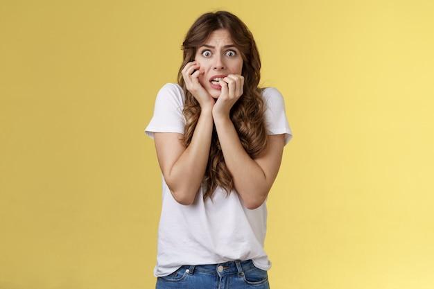 Mädchen in panik verängstigt ängstlich unsicher beißende fingernägel starren die kamera erschrocken zusammenbeißende zähne zitternde angst berühren das gesicht nervös fühlen sich unsicher verängstigt stehen gelber hintergrund