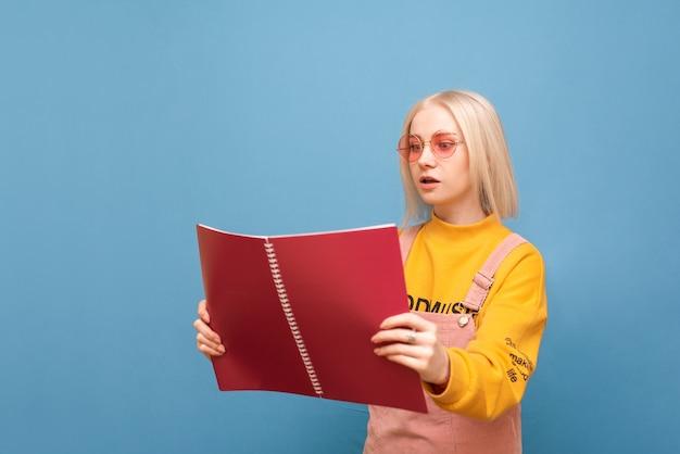 Mädchen in rosa brille und heller freizeitkleidung, von angesicht zu angesicht mit einer ernsten notiz auf blau schauend