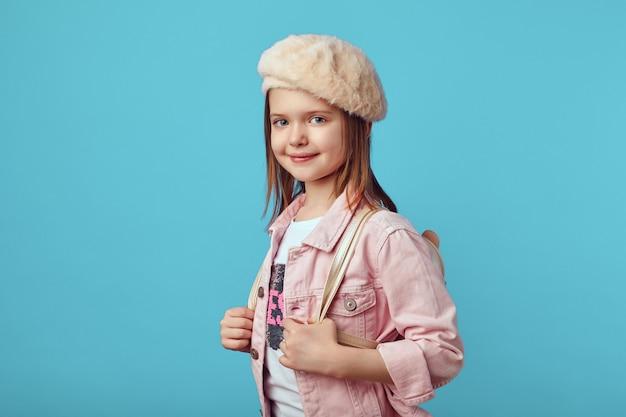Mädchen in rosa jacke und hut, blick in die kamera vor blauem hintergrund