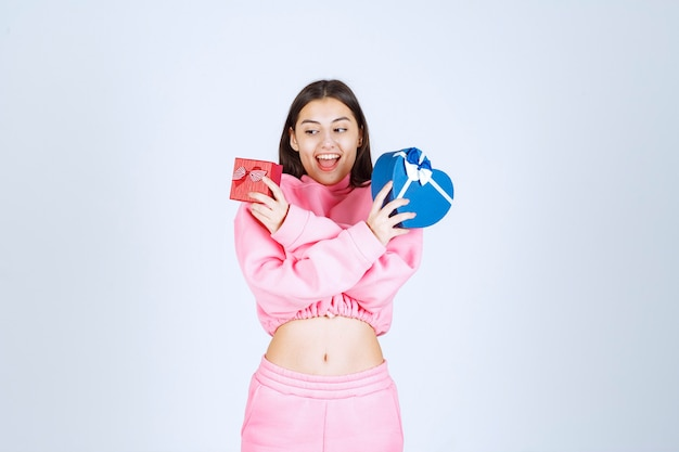 Mädchen in rosa pyjamas, die geschenkboxen des roten und blauen herzens in beiden händen halten.