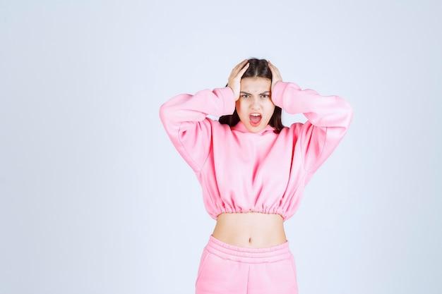 Mädchen in rosa pyjamas hält ihren kopf, wenn sie erschöpft ist oder kopfschmerzen hat.