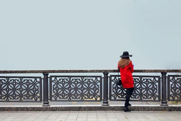 Mädchen in rotem mantel und hut steht an einem kalten herbstmorgen neben dem geländer und schaut in den nebel