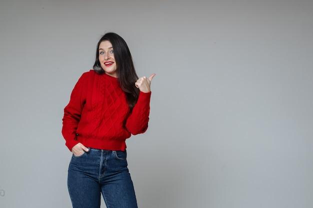Mädchen in rotem pullover und jeans, die auf leerzeichen zeigen.