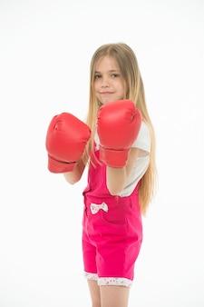 Mädchen in roten boxhandschuhen, starken geist trainierend. kind im rosa overall isoliert auf weißem hintergrund. kind mit ernstem gesicht, das bereit ist, zu kämpfen. selbstverteidigungsstunde, kleiner boxer vor dem kampf.