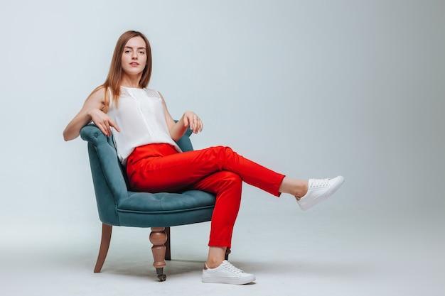 Mädchen in roten hosen sitzt auf einem stuhl auf hellgrauem hintergrund